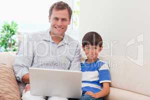 Father and son with laptop on the sofa