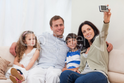 Mother taking a family picture on the couch