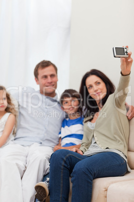 Mother taking family photograph on the sofa