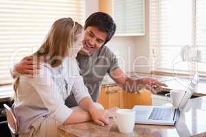 Couple having tea while using a laptop