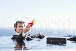 Cheerful businessman relaxing in a swimming pool with a cocktail