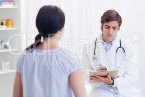 Physician taking notes while patient is talking