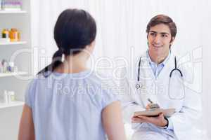 Smiling physician talking with patient