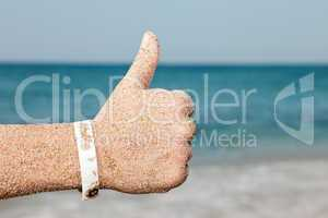 Hand gesturing thumb up on sea beach