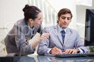 Businessman taking notes while getting explanation by colleague