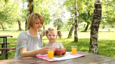 mother and daughter eat and drink in park