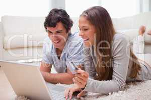 Couple lying on the floor with laptop booking holidays