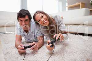Couple playing video games on the floor