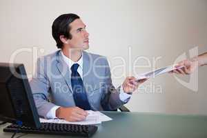 Businessman giving paperwork to colleague