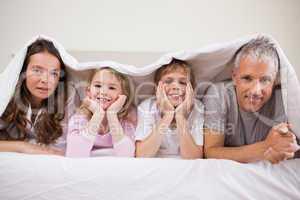 Family lying under a duvet