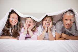 Playful family lying under a duvet