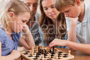 Close up of serious children playing chess in front of their par