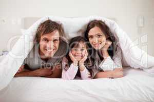 Smiling parents lying under a duvet with their daughter