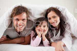 Parents lying under a duvet with their daughter