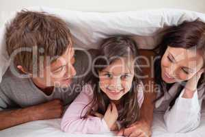 Cheerful family lying under a duvet
