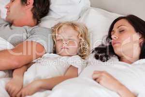 Boy sleeping between his parents