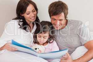 Happy parents reading a story to their daughter