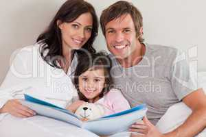 Smiling parents reading a story to their daughter