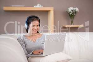 Woman enjoys listening to music on her laptop