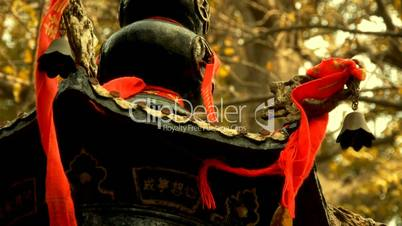 Dragon and metal bell on censer tower,Red ribbon blowing in wind,Trees,shade.