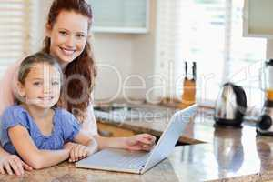 Mother and daughter surfing the internet in the kitchen