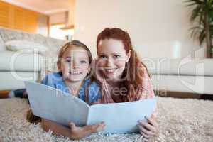 Mother and daughter looking at periodical