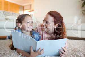Mother and daughter with periodical on the floor