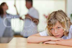Worried looking boy with fighting parents behind him