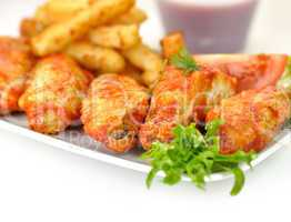 hot chicken wings with fried potatoes and sauce