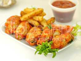 hot chicken wings with fried potatoes