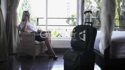 Businesswoman talking on mobile phone in hotel room