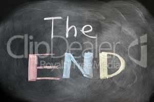 The end - handwritten with chalk on a blackboard with eraser smudges