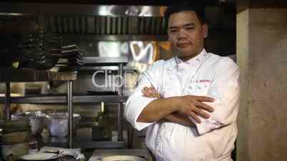 Asian chef cooking and smiling in restaurant kitchen