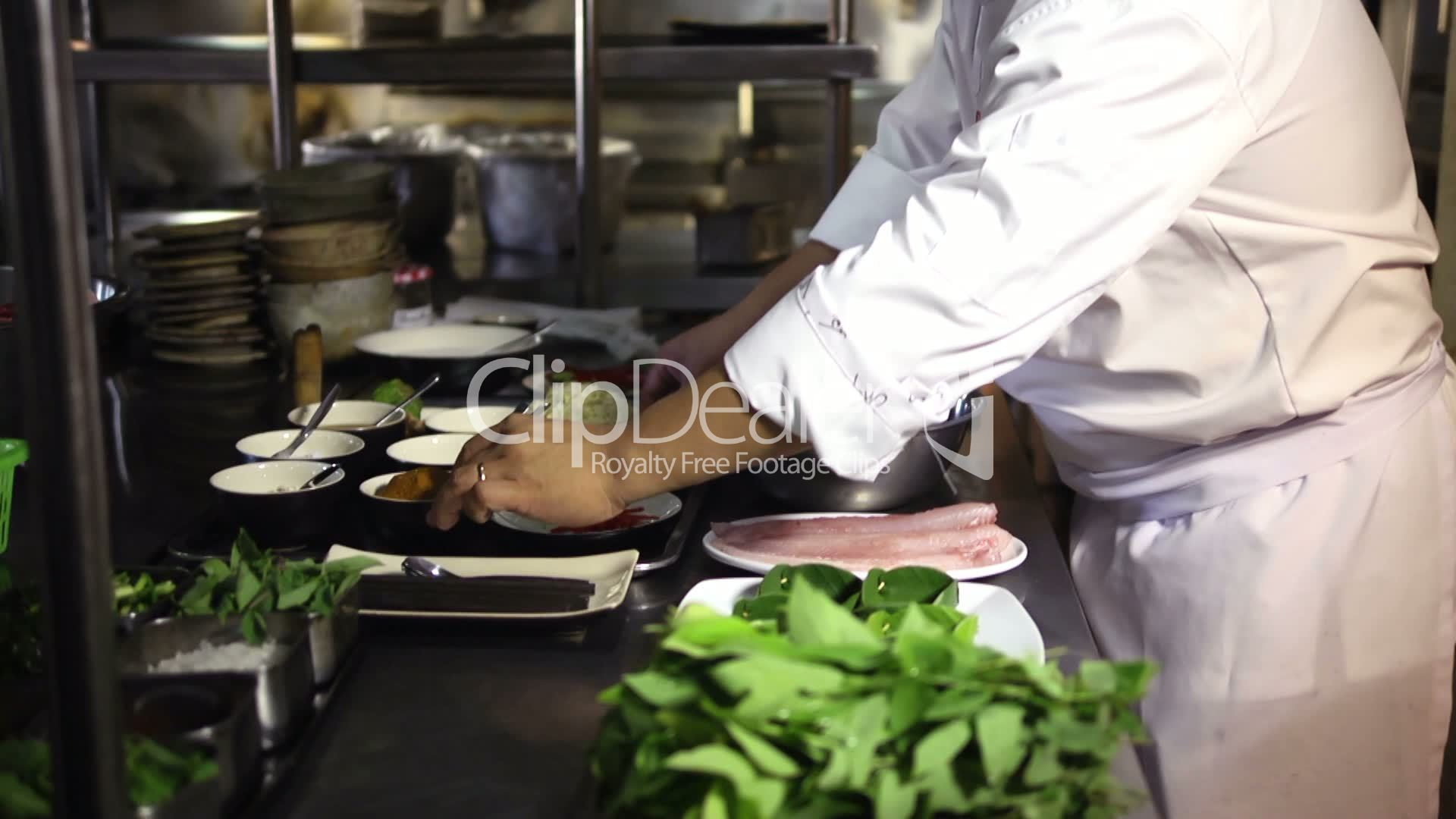 Restaurant Kitchen Terms asian chef cooking and smiling in restaurant kitchen: royalty-free