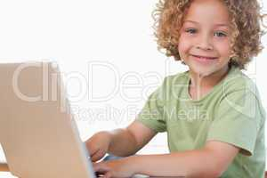 Smiling boy using a notebook