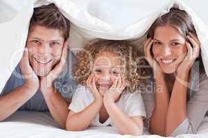 Family posing under a duvet