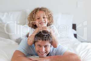 Child lying on fathers back