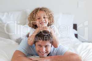 Child lying on fathers back