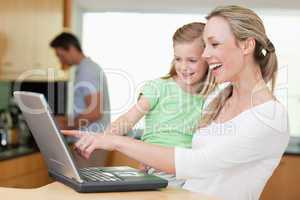 Happy mother and daughter using laptop with father in the backgr