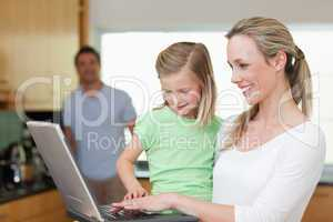 Happy mother and daughter surfing the web with father in the bac
