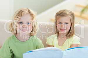 Siblings reading booklet on the sofa