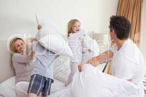 Playful family having a pillow fight in the bedroom