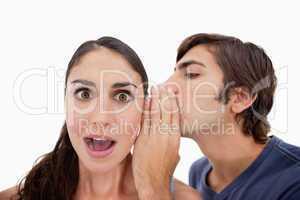 Man whispering something shocking to his fiance