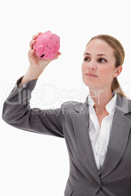 Bank employee taking close look at piggy bank