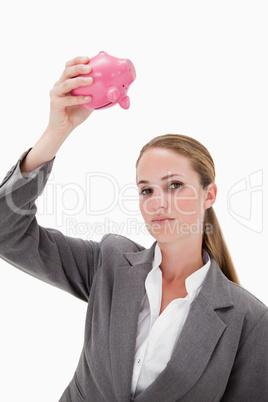 Bank employee holding piggy bank over her head