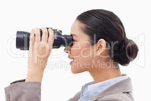 Side view of a businesswoman looking through binoculars