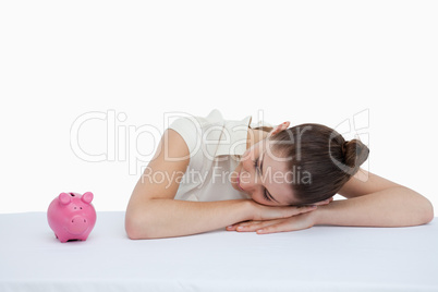 Businesswoman leaning on her desk looking at a piggy bank