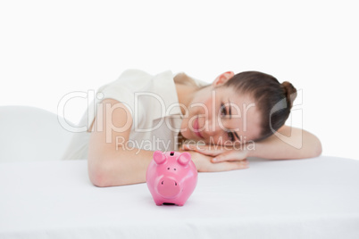 Smiling businesswoman leaning on her desk with a piggy bank