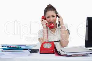 Overbooked businesswoman answering the phones