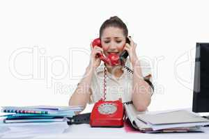 Stressed businesswoman answering the phones